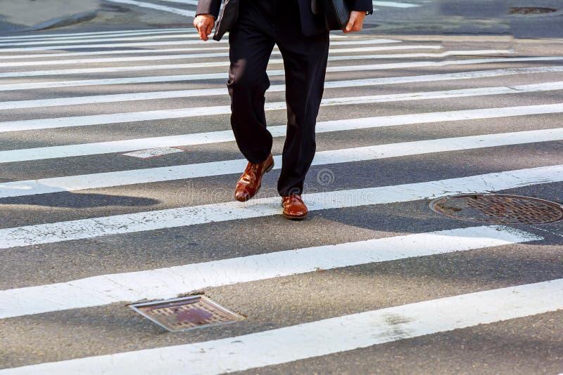 Επιχειρηματίας με τη βιασύνη χαρτοφυλάκων για να διασχίσει το δρόμο στοκ φωτογραφίες