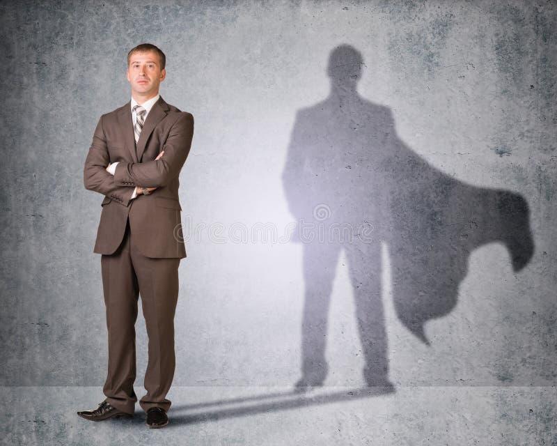 Επιχειρηματίας με τη σκιά στο ακρωτήριο στοκ εικόνες