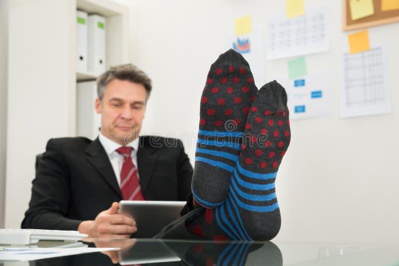 Επιχειρηματίας με τις κάλτσες στα πόδια του που χρησιμοποιούν την ψηφιακή ταμπλέτα στοκ εικόνες με δικαίωμα ελεύθερης χρήσης