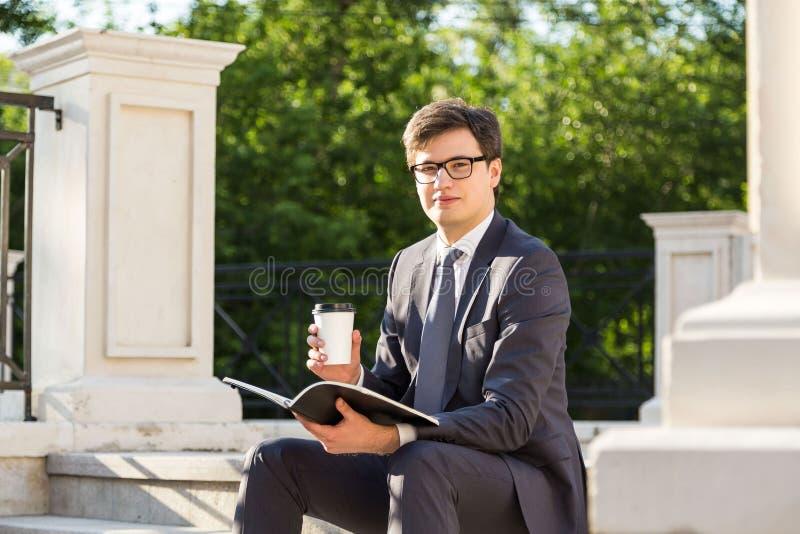Επιχειρηματίας με τον καφέ και το σημειωματάριο στοκ φωτογραφίες