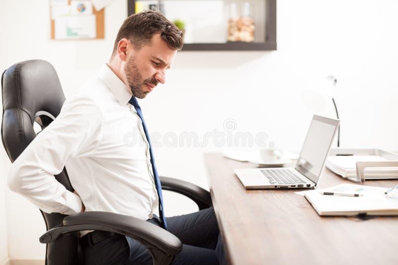 Επιχειρηματίας με τον πόνο στην πλάτη στο γραφείο στοκ εικόνα με δικαίωμα ελεύθερης χρήσης