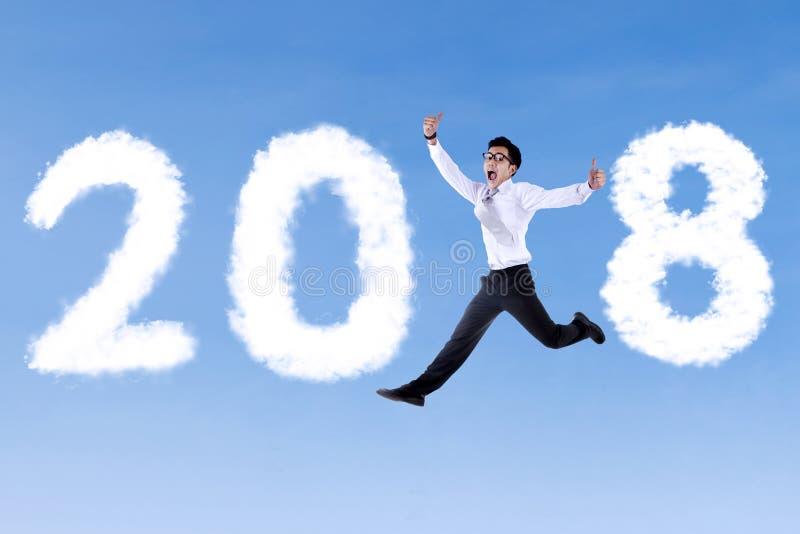 Επιχειρηματίας με τους αντίχειρες επάνω και τους αριθμούς 2018 στοκ εικόνα με δικαίωμα ελεύθερης χρήσης