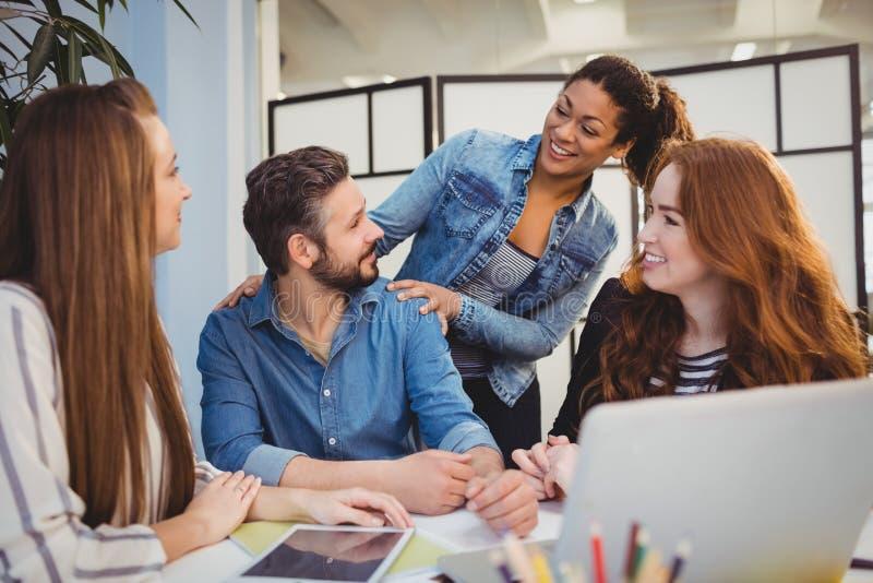 Επιχειρηματίας με τους ευτυχείς θηλυκούς συναδέλφους στο γραφείο στοκ φωτογραφία