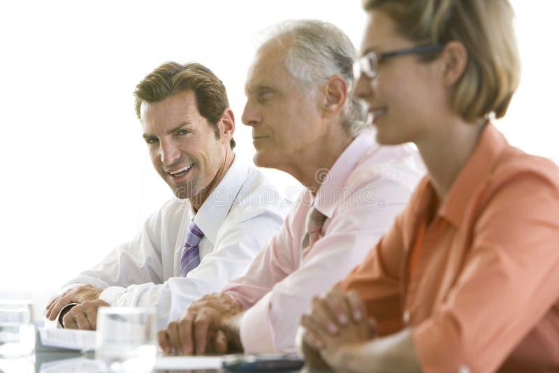Επιχειρηματίας με τους συναδέλφους στη αίθουσα συνδιαλέξεων στοκ φωτογραφία