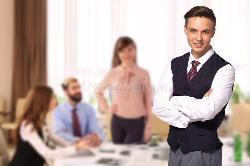 Επιχειρηματίας με τους συναδέλφους στο υπόβαθρο στην αρχή στοκ εικόνες