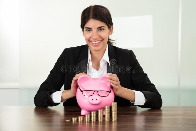 Επιχειρηματίας με τους σωρούς piggybank και νομισμάτων στοκ φωτογραφία
