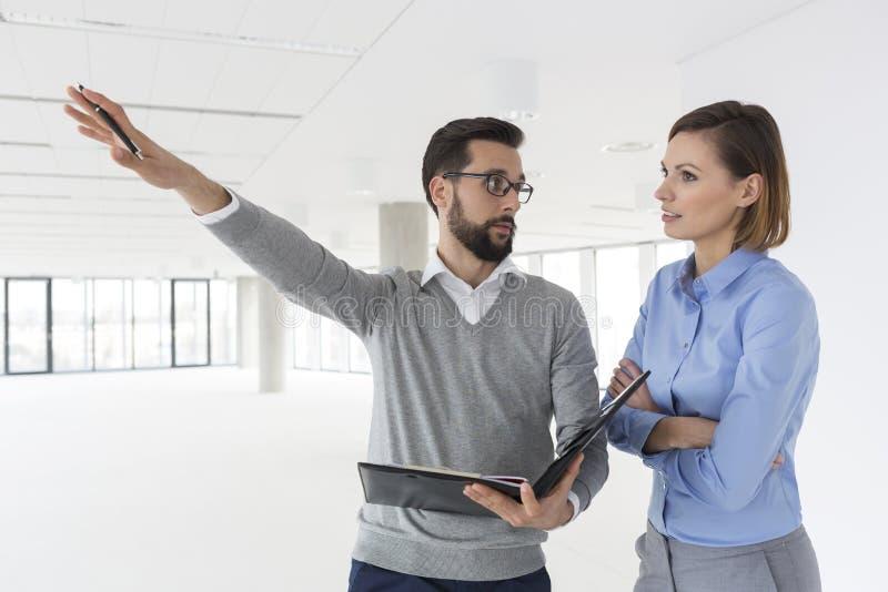 Επιχειρηματίας με το αρχείο που εξηγεί στο συνάδελφο στο νέο γραφείο στοκ εικόνα με δικαίωμα ελεύθερης χρήσης