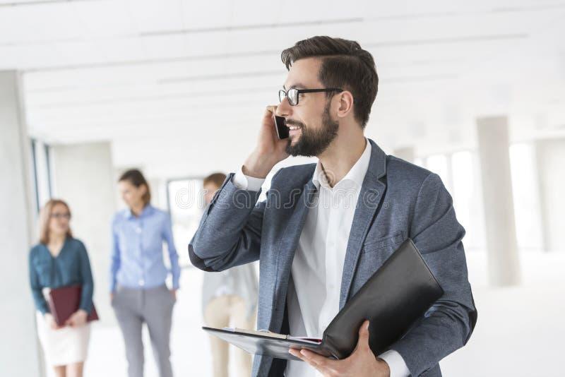 Επιχειρηματίας με το αρχείο που μιλά στο κινητό τηλέφωνο ενάντια στους συναδέλφους στο νέο γραφείο στοκ εικόνα