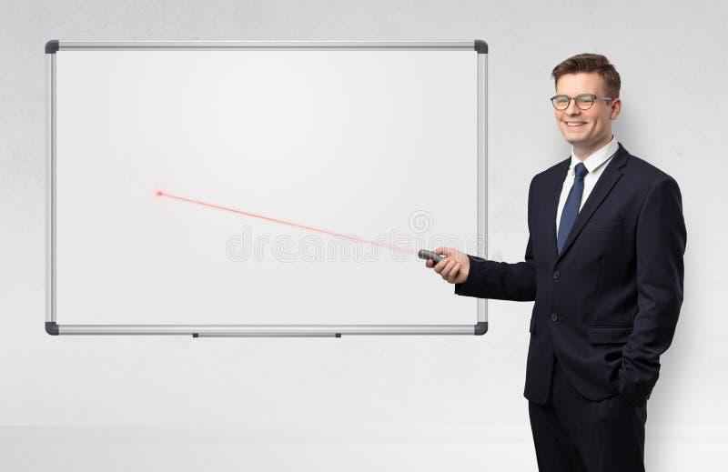 Επιχειρηματίας με το δείκτη λέιζερ και copyspace τον άσπρο πίνακα στοκ εικόνες