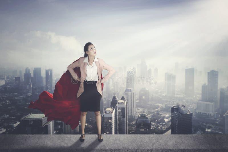 Επιχειρηματίας με το κόκκινο ακρωτήριο με το σύγχρονο υπόβαθρο πόλεων στοκ εικόνα με δικαίωμα ελεύθερης χρήσης