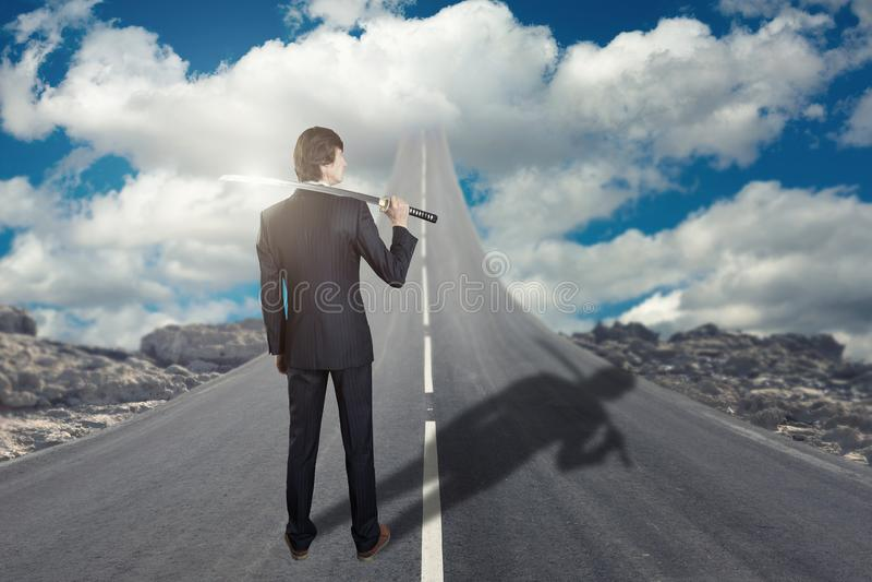 Επιχειρηματίας με το ξίφος katana που στέκεται στο δρόμο που πηγαίνει επάνω στον ουρανό στοκ φωτογραφίες