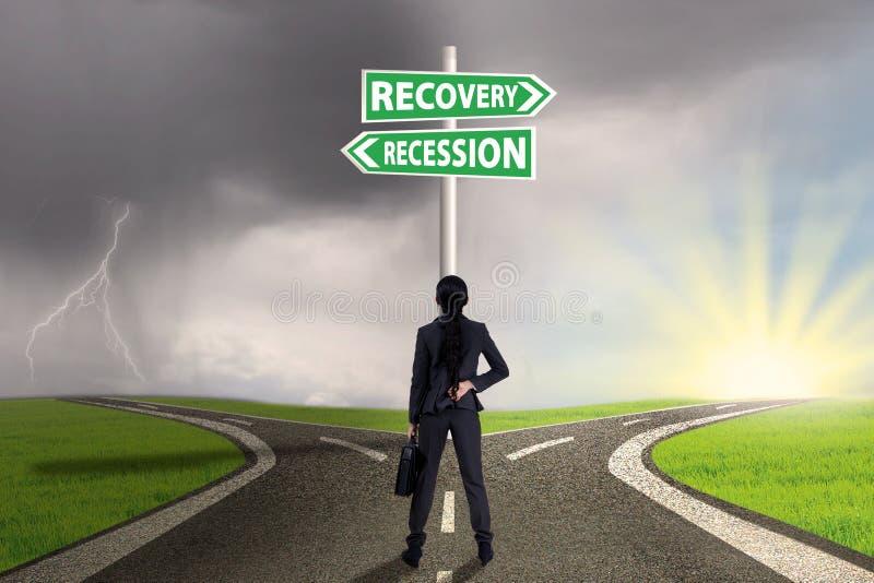 Επιχειρηματίας με το οδικό σημάδι στη χρηματοδότηση αποκατάστασης ή υποχώρησης στοκ φωτογραφία με δικαίωμα ελεύθερης χρήσης