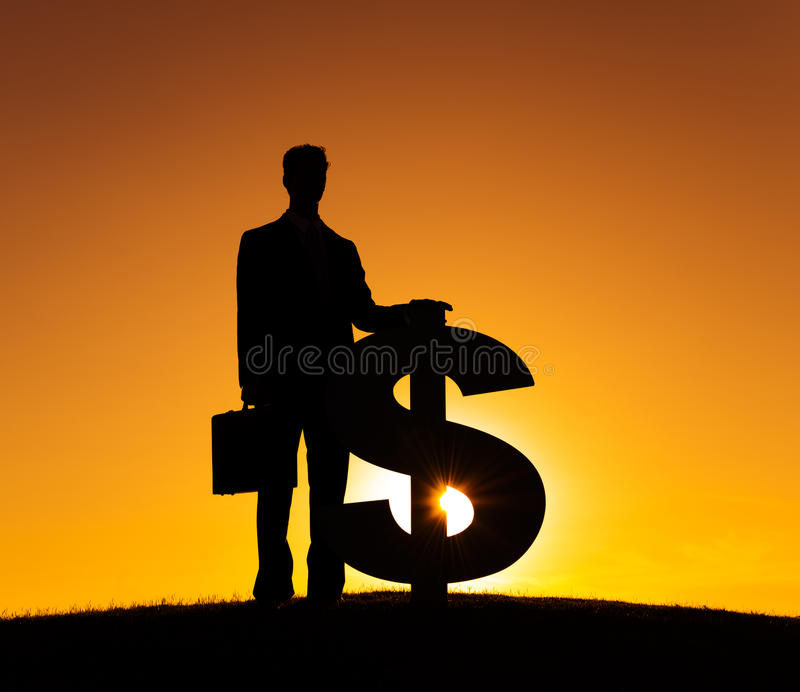 Επιχειρηματίας με το πίσω LIT νομίσματος σημαδιών δολαρίων στοκ εικόνα