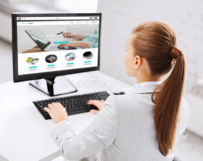 Επιχειρηματίας με το σε απευθείας σύνδεση κατάστημα στον υπολογιστή γραφείων στοκ φωτογραφία