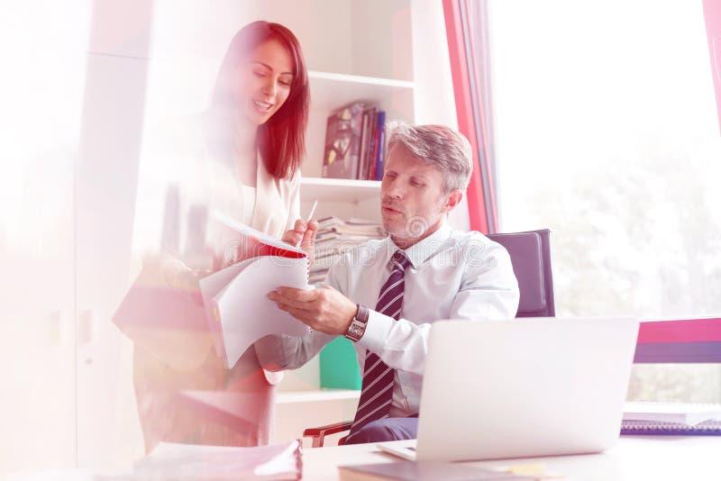 Επιχειρηματίας με το συνάδελφο που αναλύει τα έγγραφα στην αρχή στοκ φωτογραφία με δικαίωμα ελεύθερης χρήσης