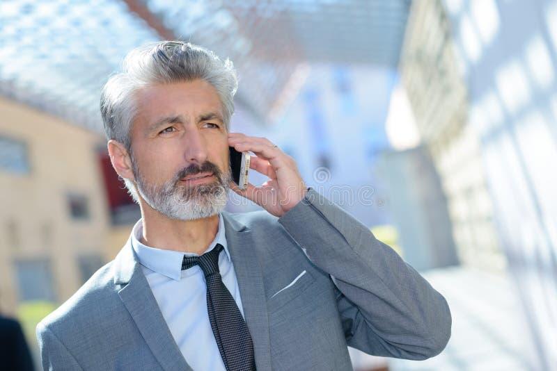 Επιχειρηματίας με το τηλέφωνο στην αρχή στοκ εικόνες με δικαίωμα ελεύθερης χρήσης