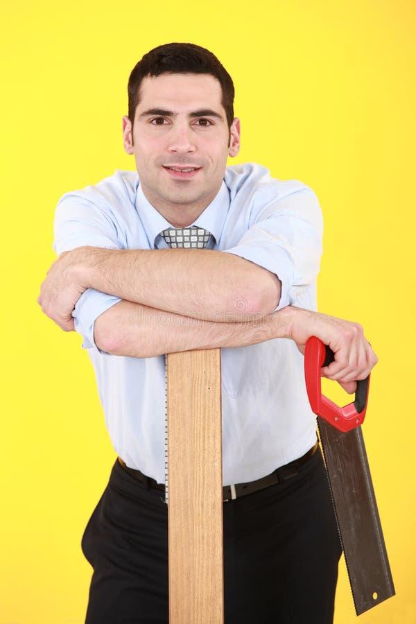 Επιχειρηματίας με το χέρι-πριόνι στοκ εικόνες