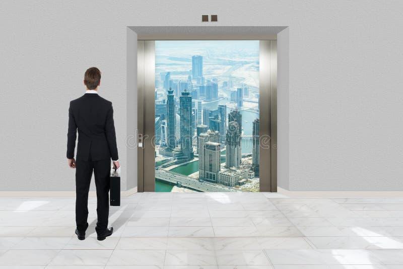 Επιχειρηματίας με το χαρτοφύλακα που εξετάζει το σύγχρονο ανελκυστήρα στοκ εικόνες με δικαίωμα ελεύθερης χρήσης