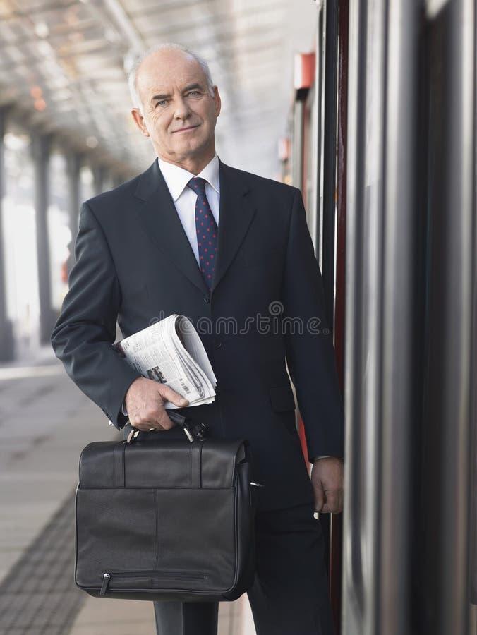 Επιχειρηματίας με το χαρτοφύλακα και εφημερίδα με το τραίνο στον κενό σταθμό στοκ εικόνες