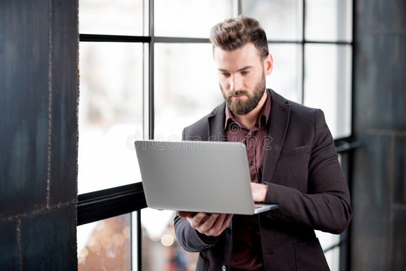 Επιχειρηματίας με το lap-top κοντά στο παράθυρο στοκ εικόνα με δικαίωμα ελεύθερης χρήσης