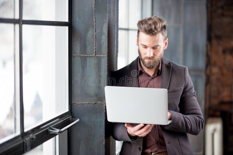 Επιχειρηματίας με το lap-top κοντά στο παράθυρο στοκ φωτογραφία