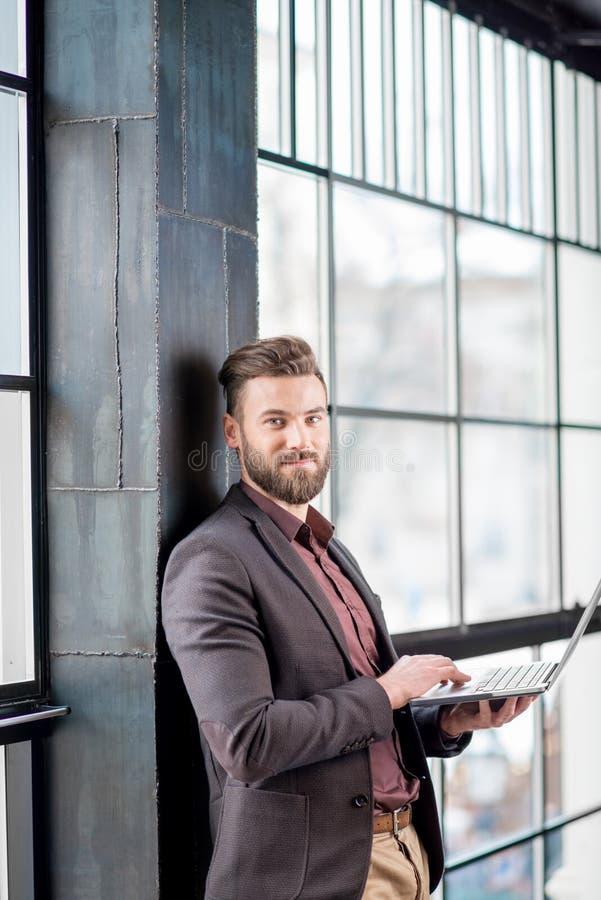 Επιχειρηματίας με το lap-top κοντά στο παράθυρο στοκ εικόνες