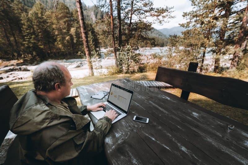 Επιχειρηματίας με το lap-top που είναι στην άδεια στοκ φωτογραφία