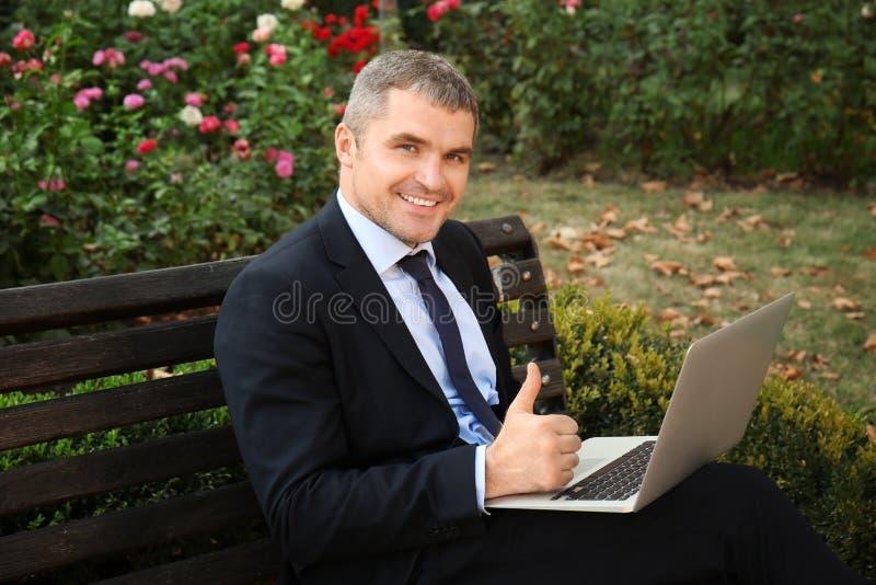 Επιχειρηματίας με το lap-top που παρουσιάζει αντίχειρας-επάνω στη χειρονομία καθμένος στον πάγκο υπαίθρια στοκ εικόνες με δικαίωμα ελεύθερης χρήσης