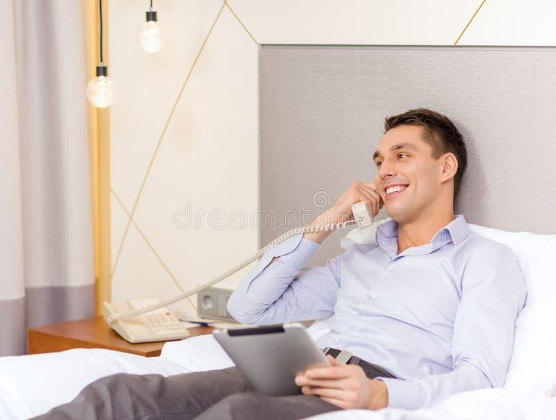 Επιχειρηματίας με το PC ταμπλετών και τηλέφωνο στο δωμάτιο ξενοδοχείου στοκ εικόνες