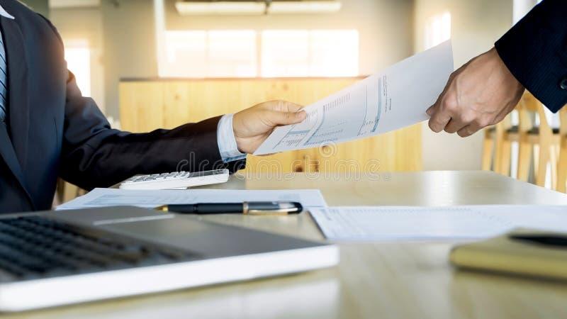 Επιχειρηματίας ο συνάδελφός του που δίνει τη σύμβαση για να διαβάσει και να υπογράψει στοκ εικόνες