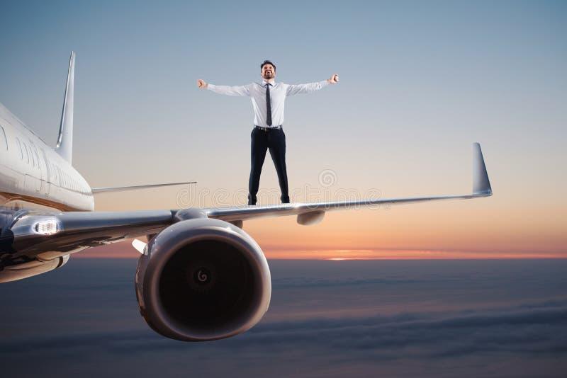 Επιχειρηματίας πέρα από μια ταλάντευση αεροπλάνων μακριά μπλε πεταλούδων έννοιας ουρανός ελευθερίας λουλουδιών πετώντας swallowta στοκ εικόνα με δικαίωμα ελεύθερης χρήσης