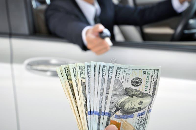 Επιχειρηματίας που δίνει σε ένα αυτοκίνητο τη βασική ανταλλαγή με τα χρήματα στοκ εικόνες