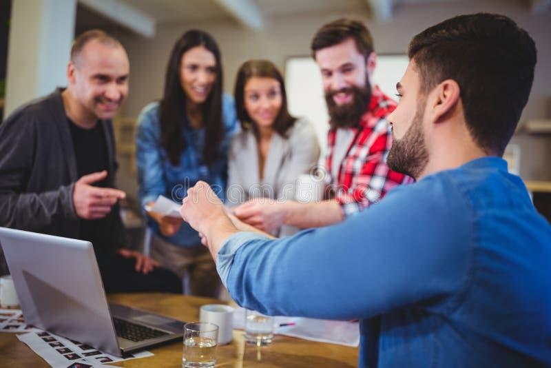 Επιχειρηματίας που δίνει τα έγγραφα στους συναδέλφους στοκ φωτογραφίες