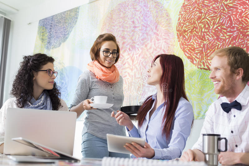 Επιχειρηματίας που δίνει τον καφέ στη γυναίκα συνάδελφος στο δημιουργικό γραφείο στοκ φωτογραφίες με δικαίωμα ελεύθερης χρήσης