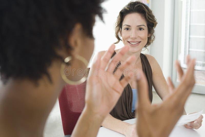 Επιχειρηματίας που ακούει τη γυναίκα συνάδελφος κατά τη διάρκεια της συνεδρίασης στοκ φωτογραφία