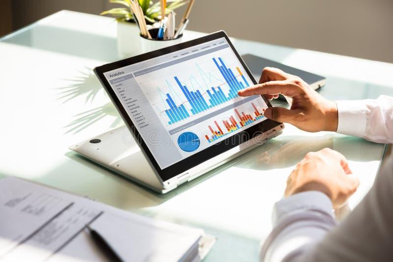 Επιχειρηματίας που αναλύει τη γραφική παράσταση στο lap-top στοκ εικόνα με δικαίωμα ελεύθερης χρήσης