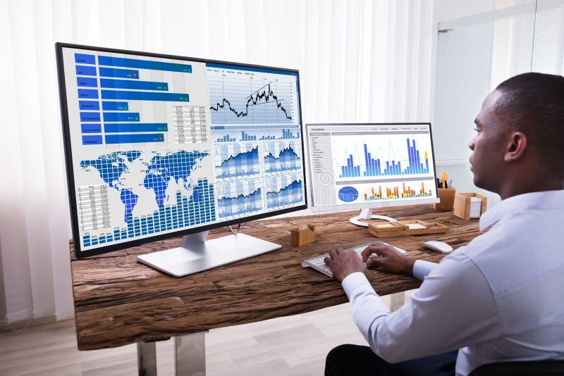 Επιχειρηματίας που αναλύει τις γραφικές παραστάσεις στους υπολογιστές στοκ εικόνα με δικαίωμα ελεύθερης χρήσης