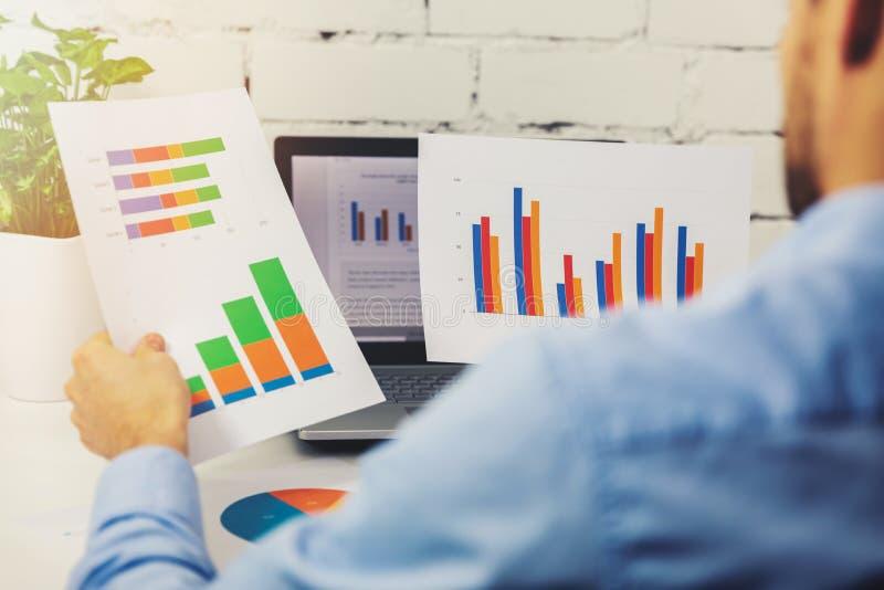 Επιχειρηματίας που αναλύει τις επιχειρησιακές οικονομικές εκθέσεις στοκ φωτογραφία