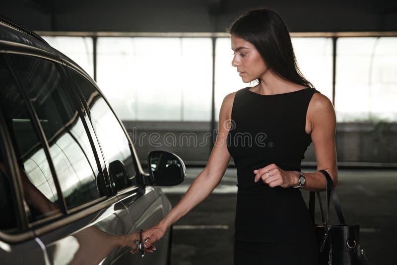 Επιχειρηματίας που ανοίγει την πόρτα του αυτοκινήτου της στο χώρο στάθμευσης στοκ φωτογραφία με δικαίωμα ελεύθερης χρήσης
