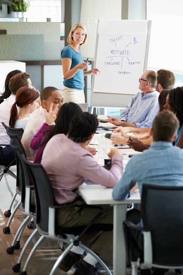 Επιχειρηματίας που απευθύνεται στη συνεδρίαση γύρω από τον πίνακα αιθουσών συνεδριάσεων στοκ φωτογραφίες