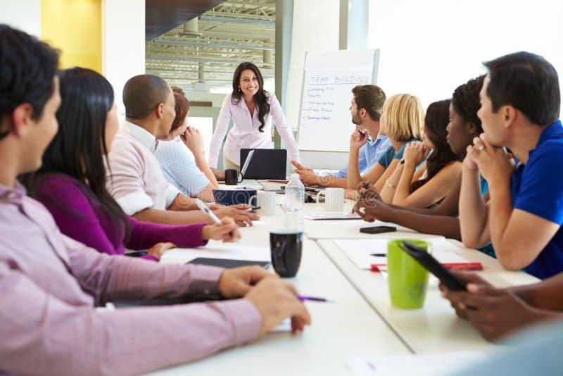 Επιχειρηματίας που απευθύνεται στη συνεδρίαση γύρω από τον πίνακα αιθουσών συνεδριάσεων στοκ φωτογραφία