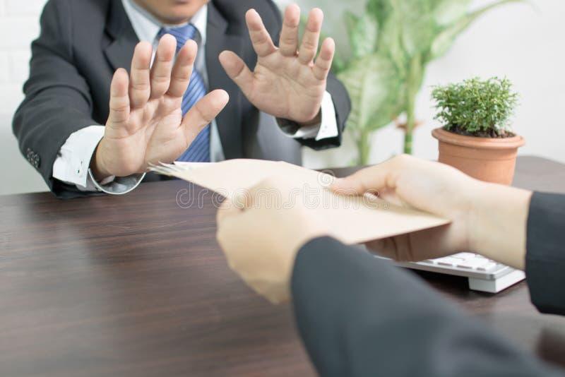 Επιχειρηματίας που αρνείται τη δωροδοκία από που κλείνει το μάτι το recievi χεριών και στάσεων στοκ εικόνα με δικαίωμα ελεύθερης χρήσης