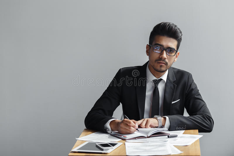 Επιχειρηματίας που γράφει σε ένα σημειωματάριο και που εξετάζει τη κάμερα σε ένα γκρίζο υπόβαθρο στοκ εικόνες