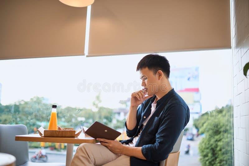 Επιχειρηματίας που γράφει στο σημειωματάριο από το παράθυρο καφέδων, που επικεντρώνεται στοκ φωτογραφία με δικαίωμα ελεύθερης χρήσης