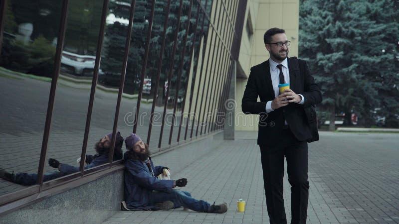 Επιχειρηματίας που δίνει τα χρήματα στους αστέγους στοκ εικόνα
