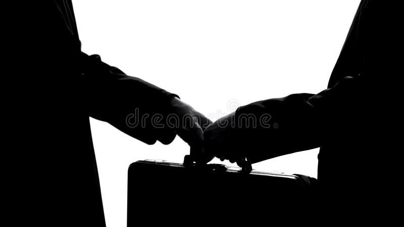 Επιχειρηματίας που δίνει τη βαλίτσα στο συνεργάτη, υπόγεια οικονομία, παράνομη διαπραγμάτευση, δωροδοκία στοκ φωτογραφία