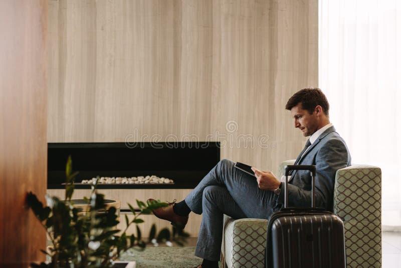 Επιχειρηματίας που διαβάζει ένα περιοδικό περιμένοντας την πτήση του στοκ φωτογραφία