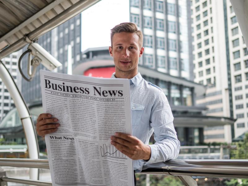 Επιχειρηματίας που διαβάζει μια εφημερίδα στον τρόπο να εργαστεί ένα πρωί, καλές ειδήσεις στοκ εικόνες