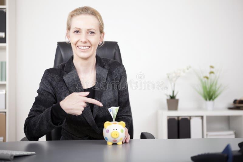 Επιχειρηματίας που δείχνει στην τράπεζα Piggy με τα μετρητά στοκ φωτογραφίες