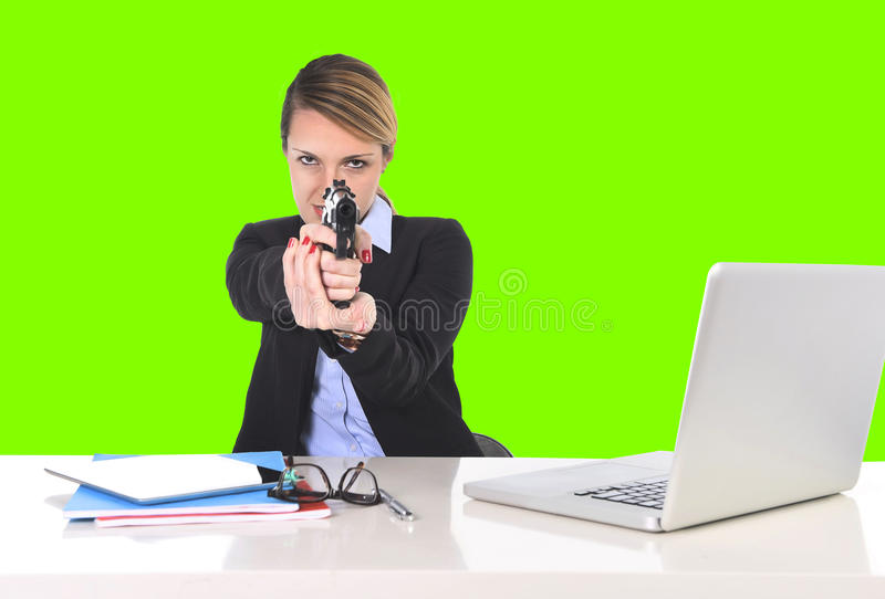 Επιχειρηματίας που δείχνει το πυροβόλο όπλο στο γραφείο γραφείων στο αυταρχικό κλειδί χρώματος τοποθέτησης στοκ φωτογραφίες